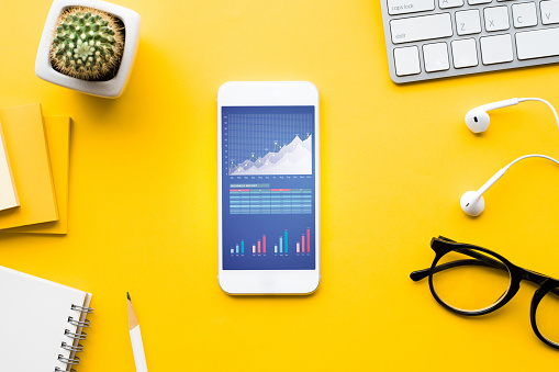 istock Top view of office desk table with graph chart on mock up smartphone 1060760900