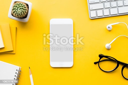 1060760900istockphoto Top view of office desk table with mock up smartphone and modern accessories,supplies on color background 1062576608