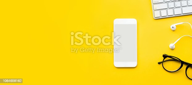 1060760900istockphoto Top view of office desk table with mock up smartphone and modern accessories,supplies on color background.flat lay design.business concepts 1064658162