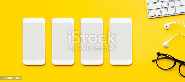 1060760900istockphoto Top view of office desk table with mock up smartphone and modern accessories,supplies on color background.flat lay design.business concepts 1065874194