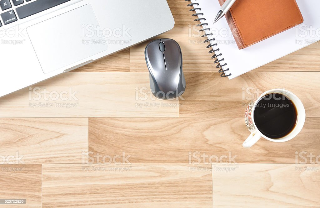 Top view of office desk with laptop, mouse, black tea, notebook, pen...