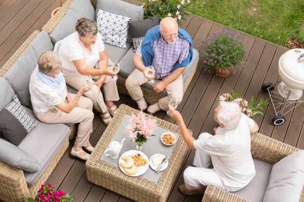 トップは昔の木製デッキの外友達レユニオンを表示します。幸せな先輩のお祝い中にトーストを作るします。 - デッキ ストックフォトと画像