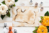Top view of old paper with yellow ghost pumpkins on wooden board. halloween concept.
