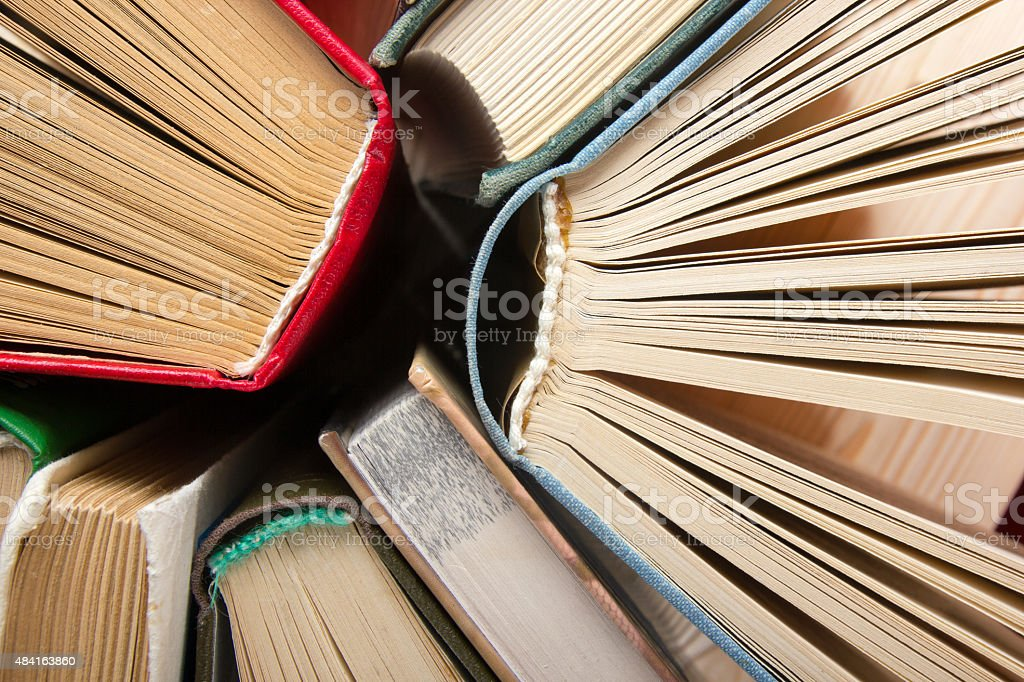 Top view of old used colorful hardback books. stock photo