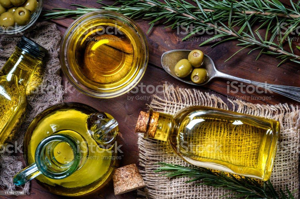 Vue supérieure des olives et des bouteilles d'huile d'olive sur la table dans une cuisine rustique - Photo de Huile d'olive libre de droits