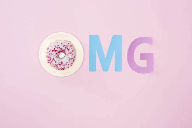 top view of omg sign made from letters and icing donut isolated on pink. chocolate donuts background in minimal style - omg stock photos and pictures
