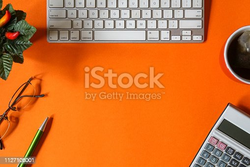 Top view office table desk in orange with keyboard, calculator, old glasses, pen, tea mug and a pot of artificial plant