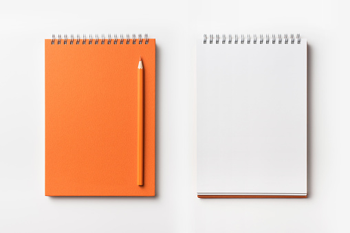 Design concept - Top view of orange spiral notebook and color pencil collection isolated on white background for mockup