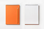 Top view of orange spiral notebook and color pencil collection