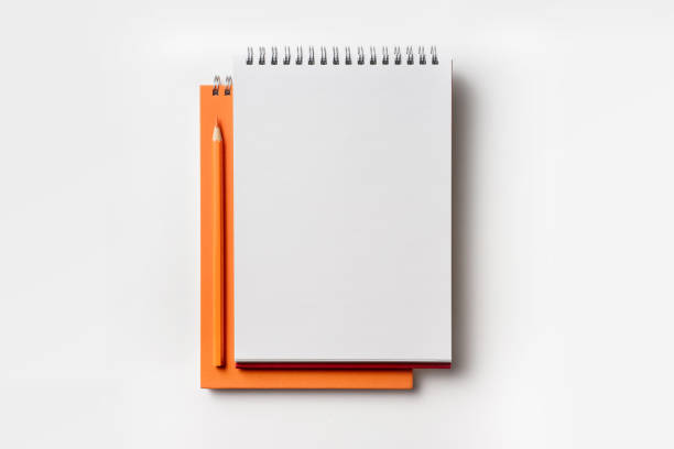 Top view of orange spiral notebook and color pencil Design concept - Top view of orange spiral notebook and color pencil collection isolated on white background for mockup note pad stock pictures, royalty-free photos & images