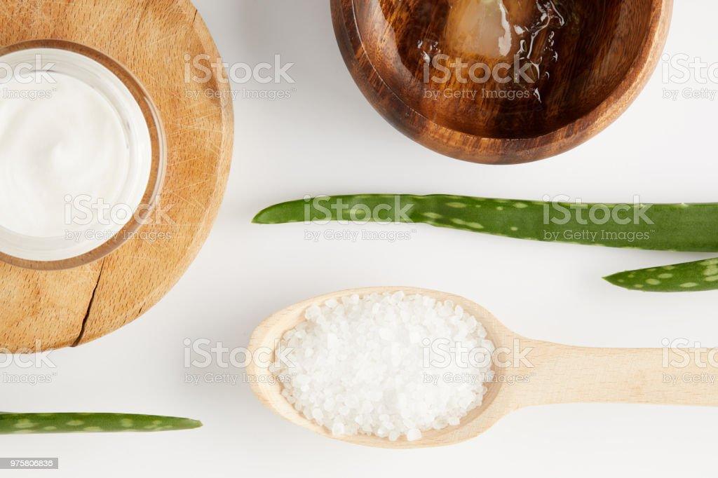 Draufsicht der Bio Creme in Container, Holzschale mit Aloe-Vera-Saft, verlässt Löffel mit Salz und Aloe vera - Lizenzfrei Aloe Stock-Foto
