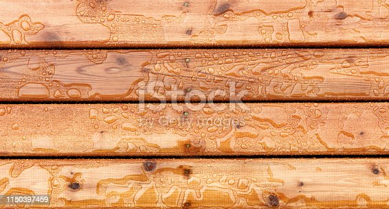 Overhead view of outdoor wooden stain deck boards with natural rain water on top of them