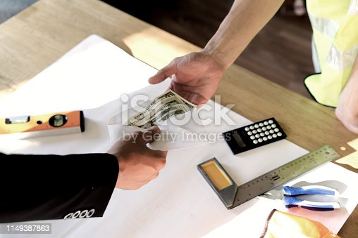 918365170 istock photo Top view of owner or boss hand giving money to employee or hired person for his wage or salary over table. 1149387863