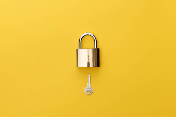 top view of padlock and key on yellow background stock photo