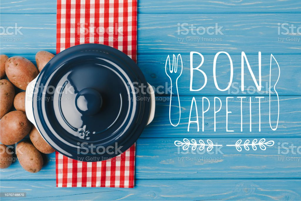 top view of pan and potatoes on blue table, bon appetit lettering stock photo