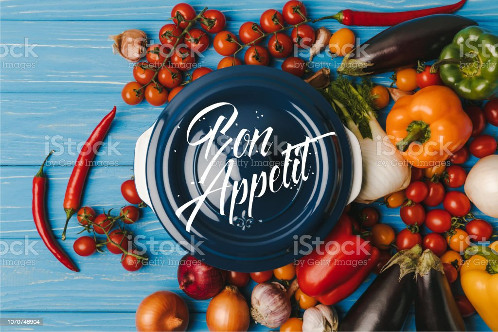 top view of pan between vegetables on blue table, bon appetit lettering stock photo
