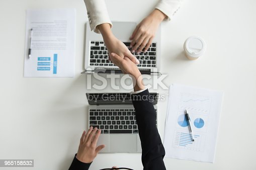 Top view of partners or CEOs handshaking, making agreement on cooperation or companies merging during board meeting in office with laptops. Concept of collaboration, partnership, closing deal