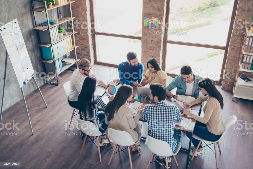 Vista superior de socios en ropa casual. Ellos se concentran, discutiendo las ideas para la nueva puesta en marcha en oficina confortable agradable - foto de stock