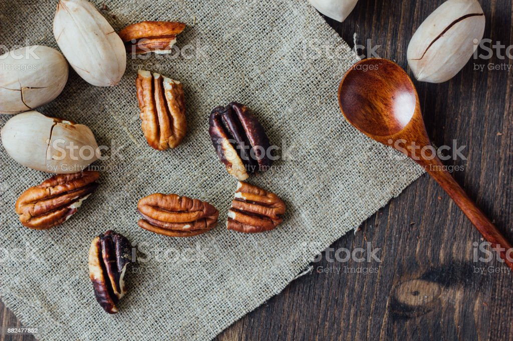 Top view of pecan nuts and wooden spoon on piece of cloth stock photo