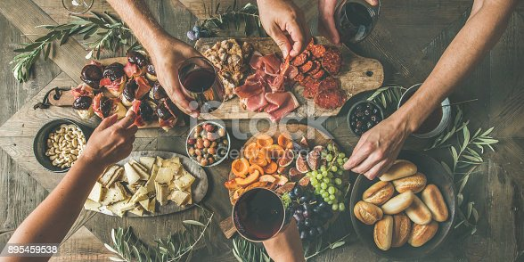 istock Top view of people drinking, eating together and holding glasses 895459538