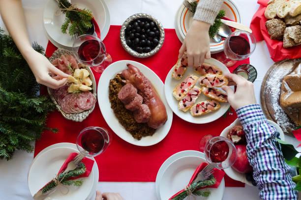 draufsicht des menschen weihnachtsessen gemeinsam genießen - italienischer weihnachten stock-fotos und bilder