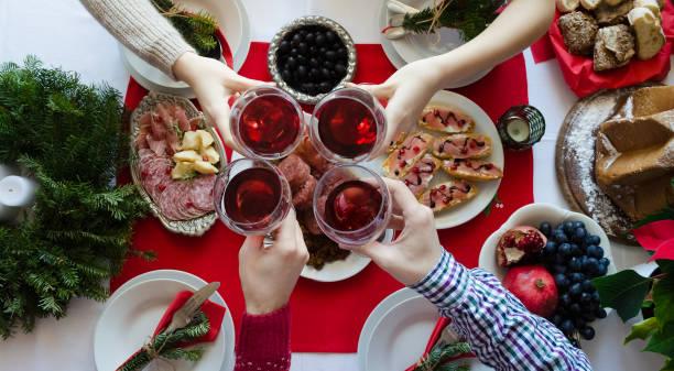 draufsicht der leute toasten mit gläser rotwein - italienischer weihnachten stock-fotos und bilder