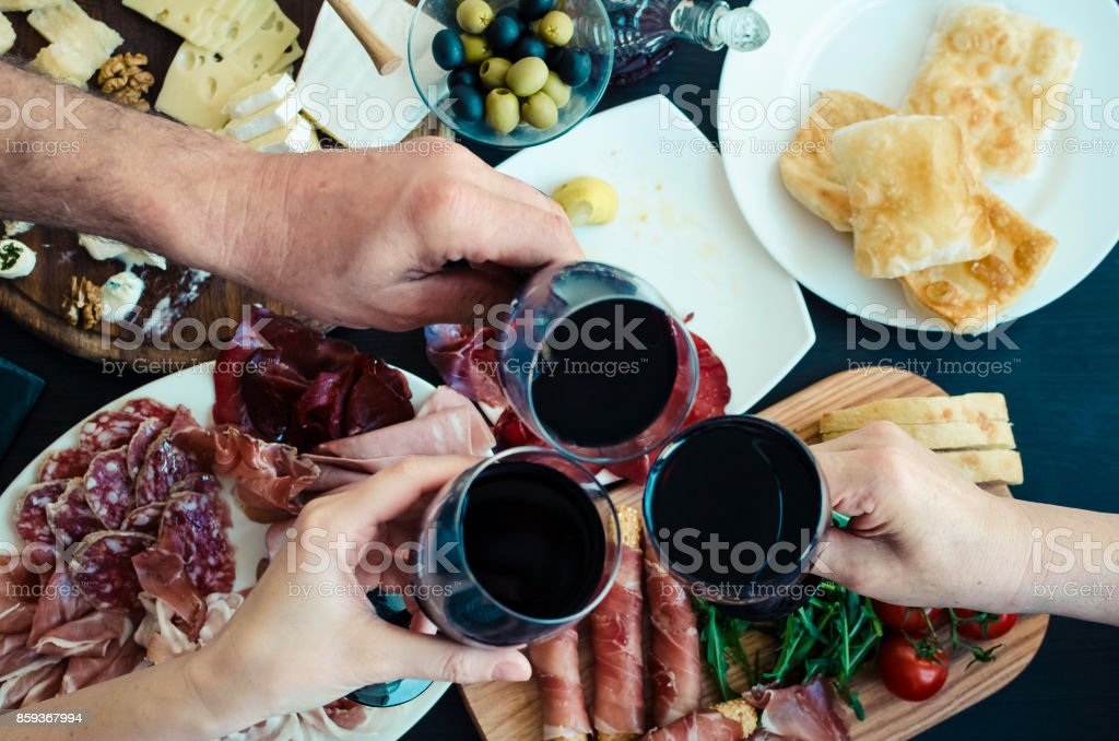 Top view of people toasting with glasses of red wine stock photo
