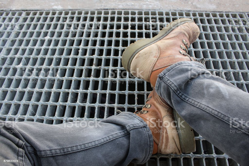 Top view of people wearing safety shoes sitting on a steel plate. Look down at the feet. stock photo