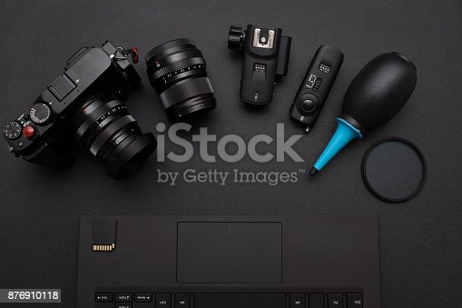 842214626istockphoto top view of photographer work space with mirrorless camera system, Dust blower, Lens filter, Wireless flash trigger, and SD card on laptop 876910118
