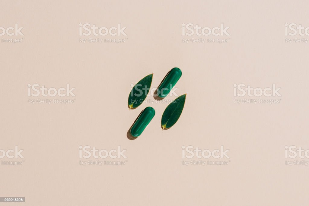 top view of phytotherapy pills and leaves on beige surface zbiór zdjęć royalty-free