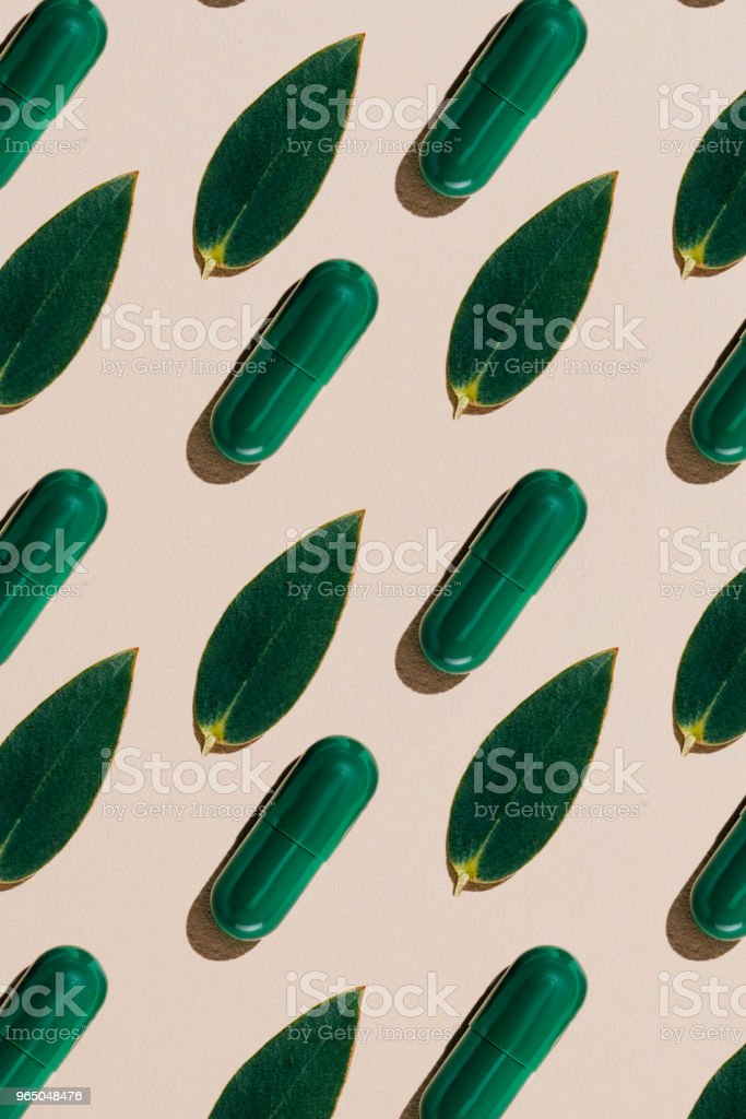top view of phytotherapy pills with green leaves in rows pattern on beige surface royalty-free stock photo