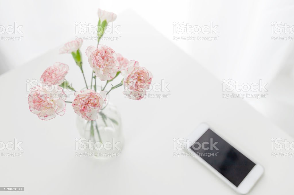 iStock & Top View Of Pink And White Carnation Flowers Vase With Smart Phone On Table Stock Photo - Download Image Now