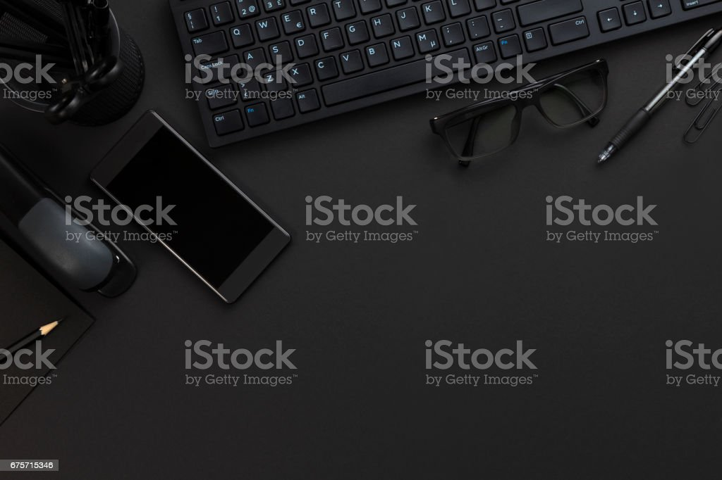 Top view of pitch black office desk with computer and supplies stock photo