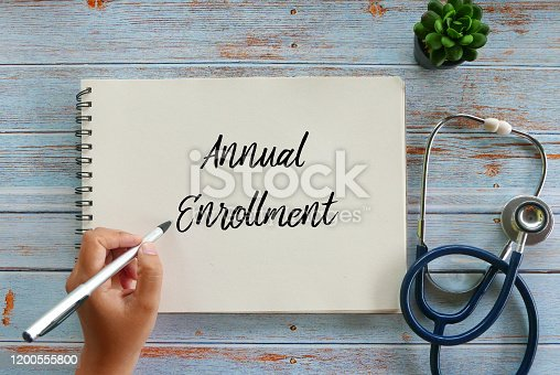 Top view of plant,stethoscope, and hand writing Annual Enrollment on notebook on wooden background.