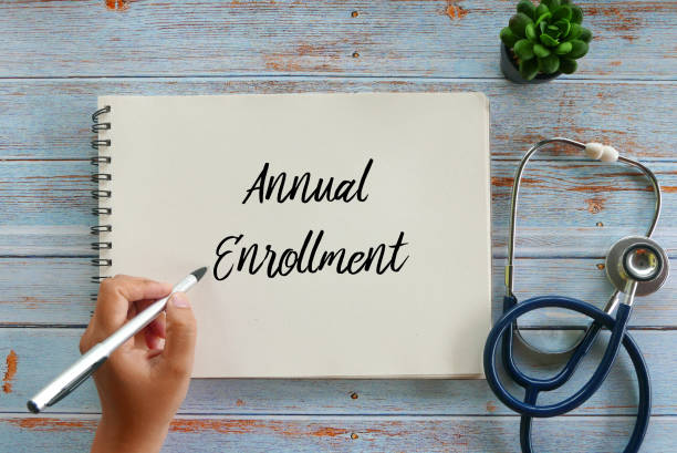 Top view of plant,stethoscope, and hand writing Annual Enrollment on notebook on wooden background. Top view of plant,stethoscope, and hand writing Annual Enrollment on notebook on wooden background. enrollment stock pictures, royalty-free photos & images