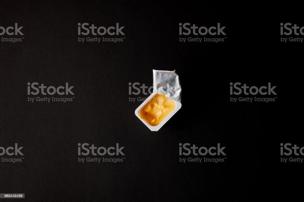Plastik kabın üzerine siyah izole peynir soslu üstten görünüm - Royalty-free Baharat Stok görsel