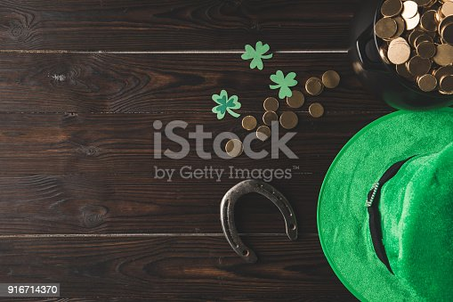 top view of pot with golden coins, horseshoe and green hat on wooden table, st patricks day concept