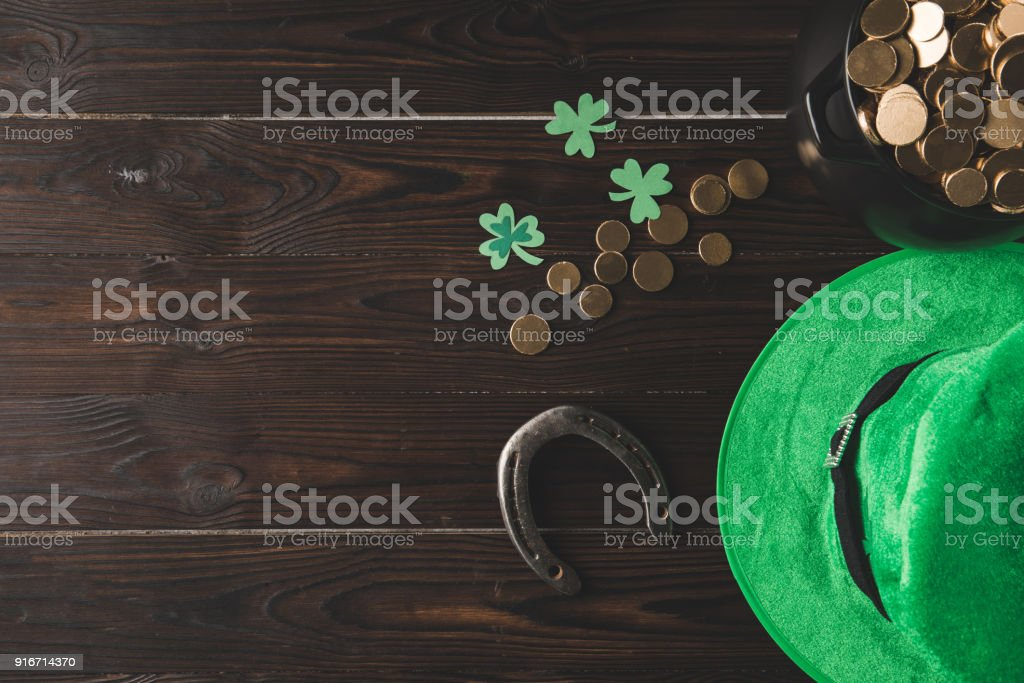 top view of pot with golden coins, horseshoe and green hat on wooden table, st patricks day concept stock photo