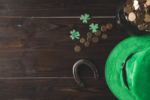 top view of pot with golden coins, horseshoe and green hat on wooden table, st patricks day concept - st patricks day stock photos and pictures