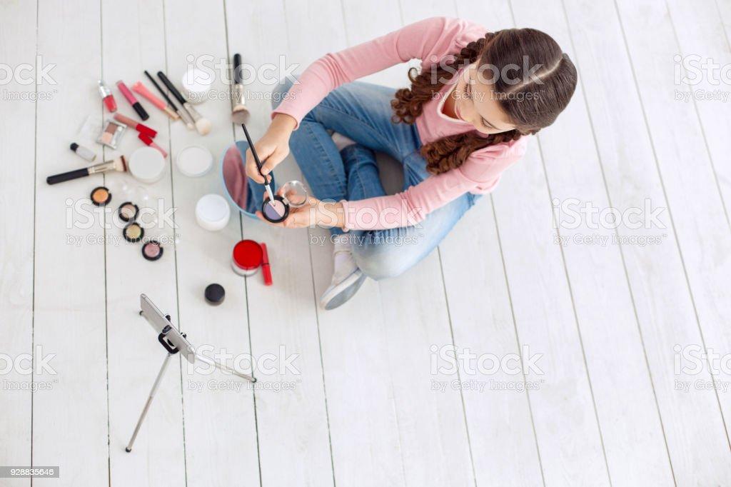 Top view of pre-teen beauty blogger choosing eye shadows stock photo