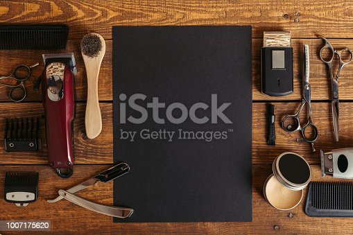 istock top view of professional barber tools and blank black card on wooden table 1007175620