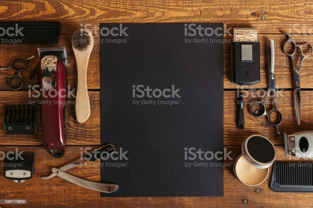 top view of professional barber tools and blank black card on wooden table stock photo