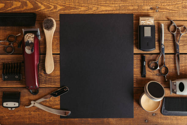 top view of professional barber tools and blank black card on wooden table - mascolinità foto e immagini stock