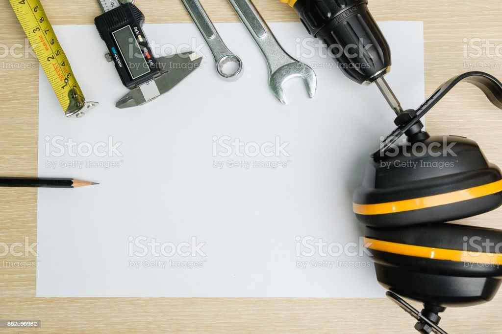 Top view of protective tool, measurement tool and wrench on blank  paper background. stock photo