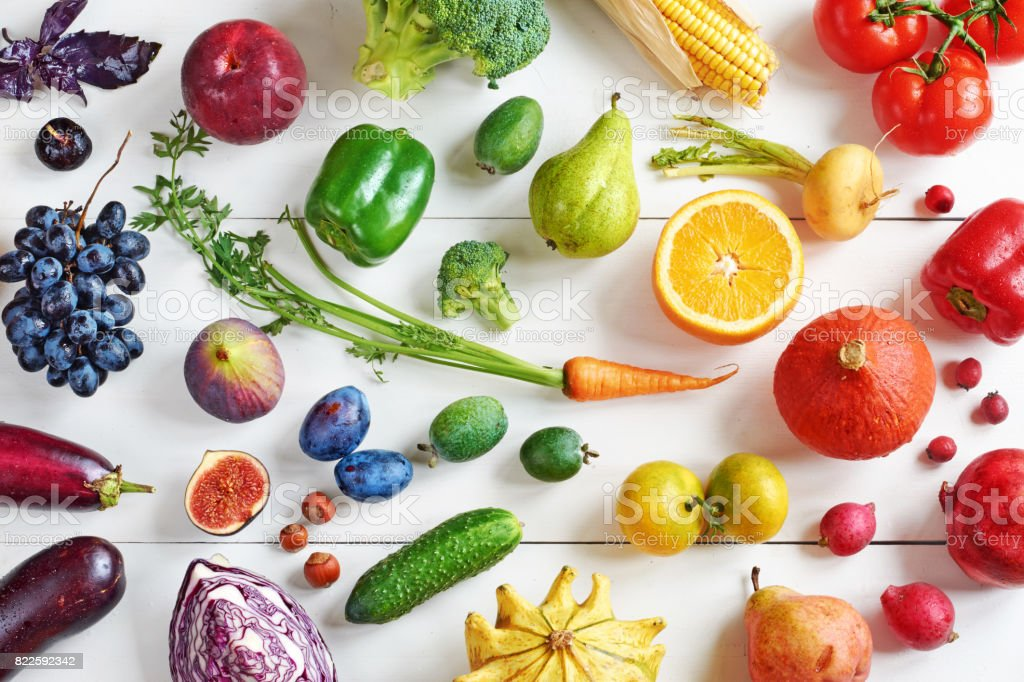 Top view of rainbow colored fruits and vegetables on a white table. stock photo
