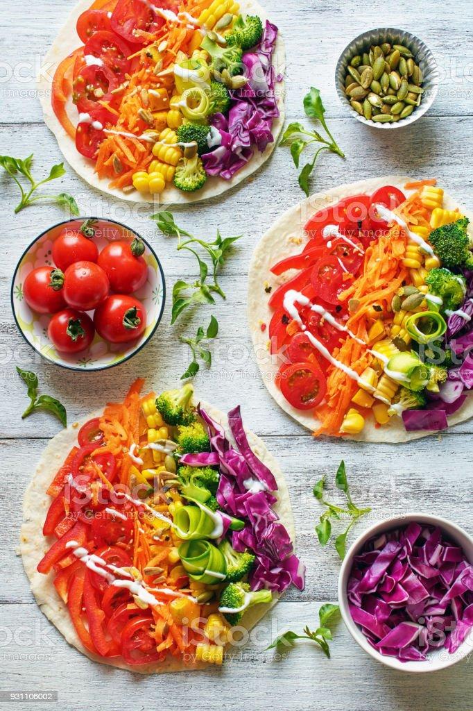 Draufsicht der Regenbogen farbige Gemüsesalat auf Fladenbrot auf weißen Tisch. – Foto