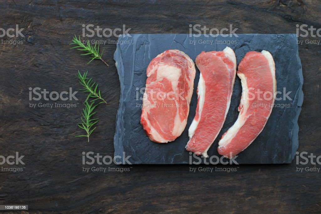 Top view of Raw beef steak with rosemary on wooden dark background, food meat or barbecue stock photo