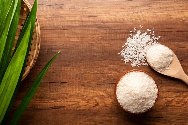 top view of raw jasmine rice in a bowl and wooden spoon on dark wooden table - pandan składnik zdjęcia i obrazy z banku zdjęć