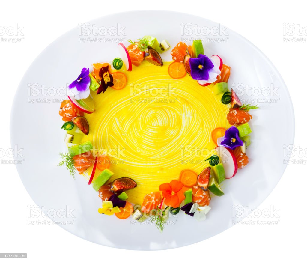 Top view of raw salmon tartare in shape of ring with fruits, vegetables, flowers stock photo