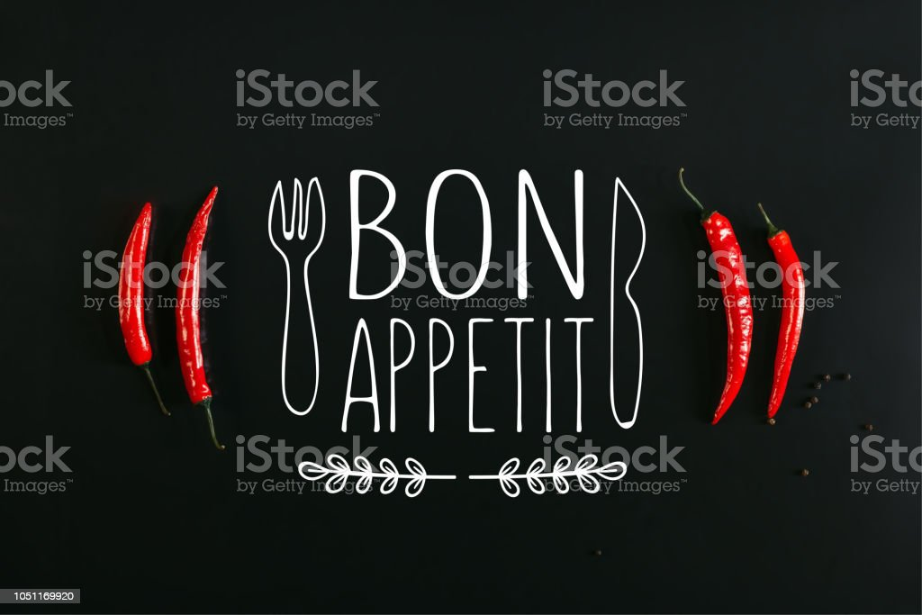 top view of red chili peppers and peppercorns on black background with 'bon appetit' lettering with fork and knife stock photo